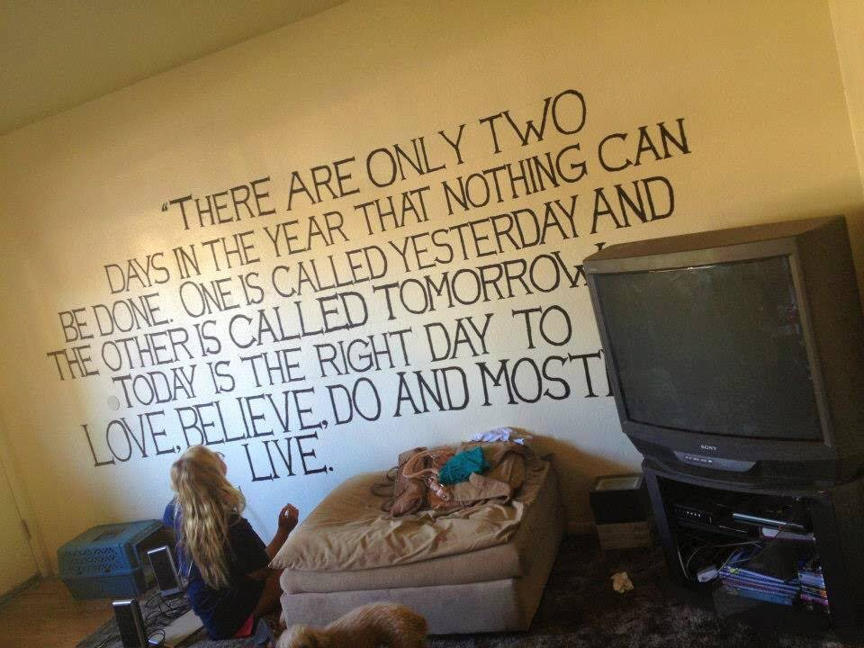 girl painting quote mural on wall