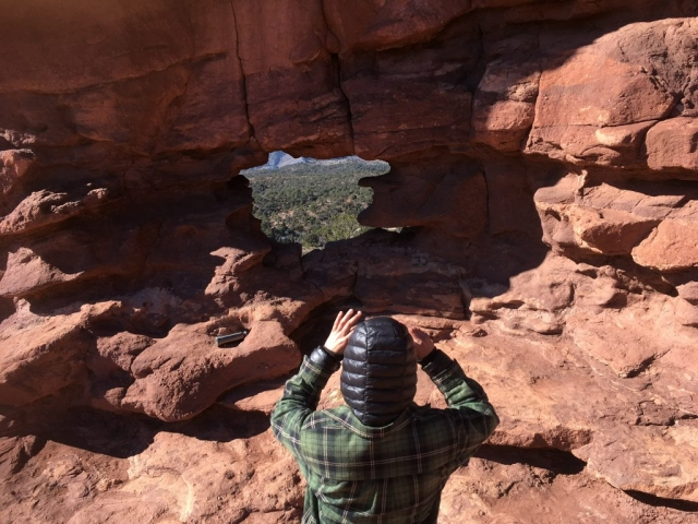 Boy in front of rocks with hole