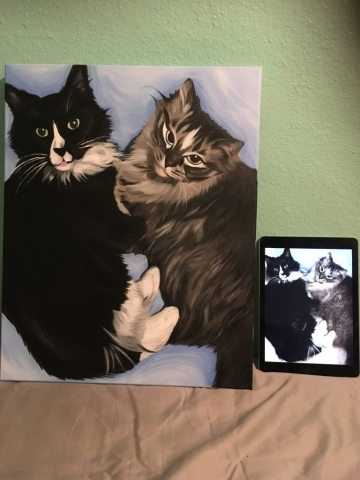 two cats in painting with picture by it