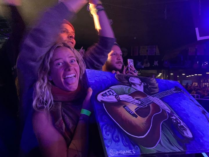 girl holding billy string painting at concert