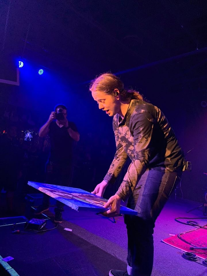 Billy Strings holding painting on stage