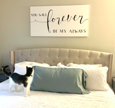 painting above bed with cat